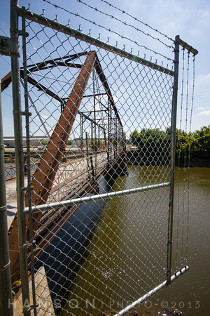 Fence panel with barbed wire blocking access to the Sylvan Island bridge.